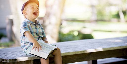 young boy laughing at book